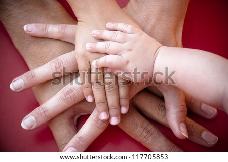 Four hands of the family,  a baby, a daughter,  a mother and a father. Concept of unity, support, protection and happiness. - stock photo