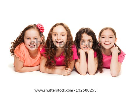 Four happy amazing 10 years old girls in pink laying on the floor, isolated on white - stock photo