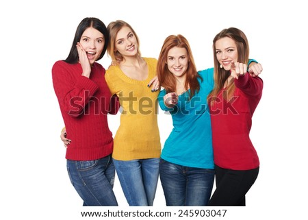 Four happy excited girls friends pointing at you, over white background - stock photo