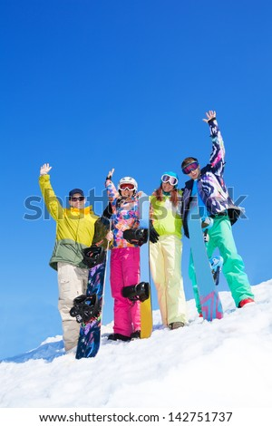 Four happy friends stand together with snowboards in snow in winter - stock photo