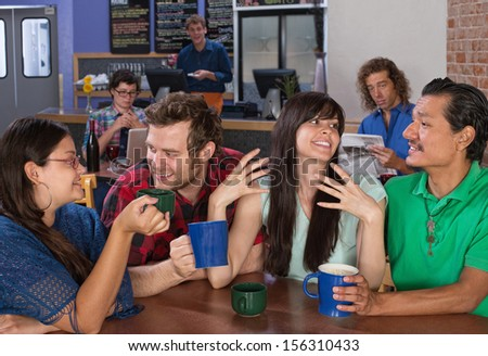 Four happy friends talking in a coffee house - stock photo