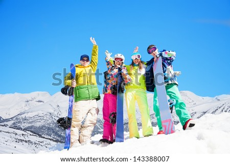 Four happy friends with snowboards standing in snow with mountains on background - stock photo