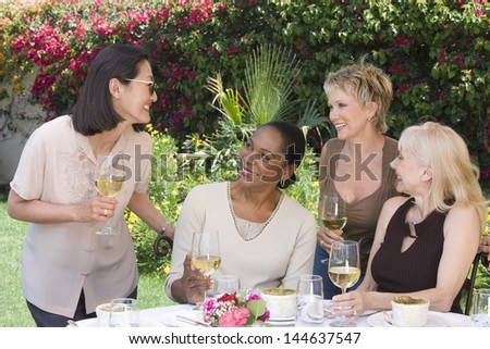 Four happy multiethnic middle aged women chatting with wine glasses at the garden party - stock photo