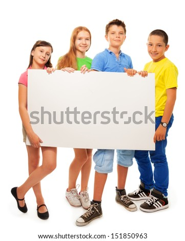 Four happy smiling friends, two girls and couple boys, holding blank white sign advertising standing in full height - stock photo