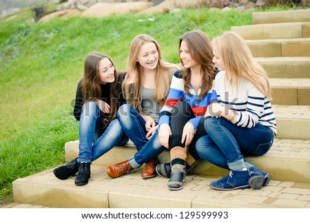 Four happy smiling teenage girls women female friends outdoors sitting on stairs - stock photo