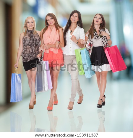 Four happy women with shopping bags isolated on white - stock photo