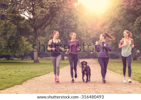 Four Healthy Young Women Jogging at the Park in the Afternoon with a Pet Dog. - stock photo