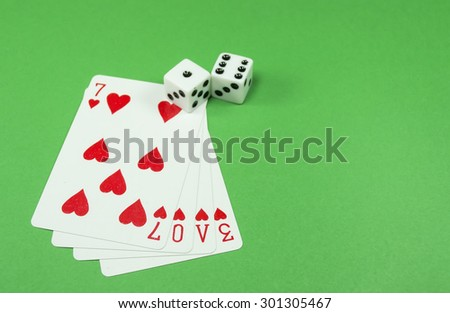 "Four hearts playing cards forming the word ""love"" and two dice, against a green background, conceptual image about love being a gamble - stock photo"