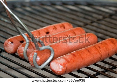 Four hot dogs on a charcoal grill with tongs about to turn one - stock photo