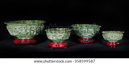 Four Jade bowls with wooden base isolated on dark background. - stock photo