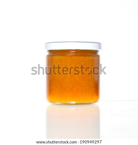 Four jars of orange jam, marmalade or sauce in a glass container with a reflection against a white background. - stock photo