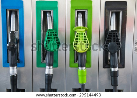 Four jet nozzles or hoses with tap for dispensing fuel at a gas station  - stock photo