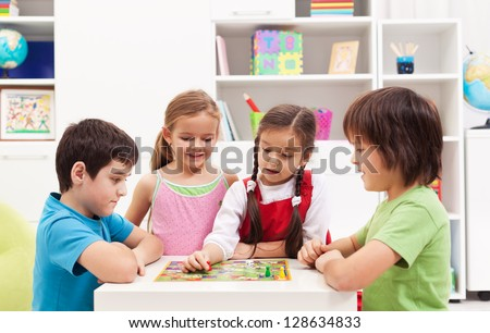 Four kids playing board game in their room - stock photo