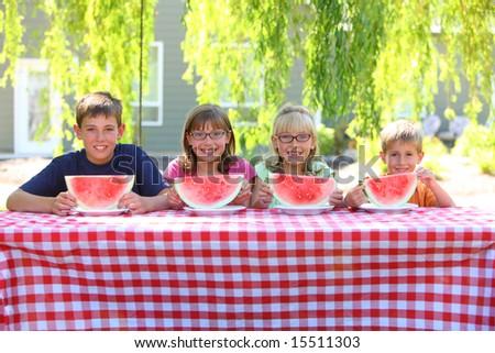 Four kids with watermelon - stock photo