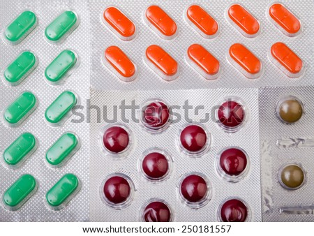 Four kinds of colorful pills in silver foil blisters - stock photo