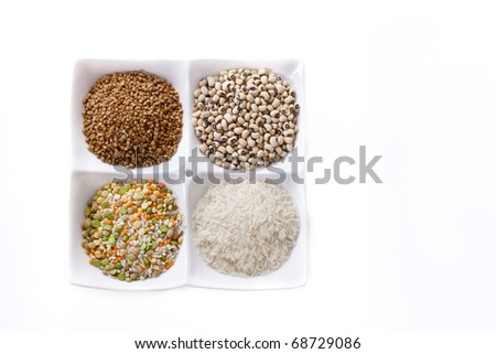 Four kinds of groats in one plate lie separately on a white background. - stock photo