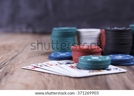 Four kings, poker chips and cards on wooden background in casino - stock photo