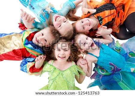 Four laughing girls and one boy, dressed in fancy dress, lie on floor head-to-head in form of flower petal - stock photo