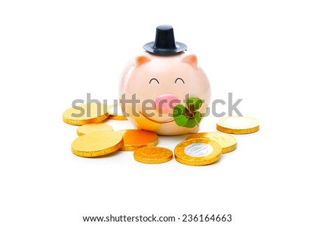 Four-leafed clover and piggybank with money - stock photo