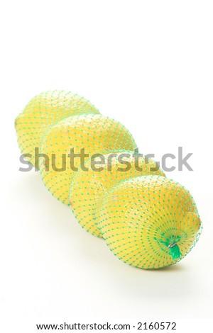 Four lemons in a green net bag - stock photo