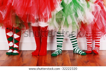 Four little girls wearing christmas socks and tutu's - stock photo