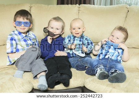 Four little kid site on the sofa - stock photo