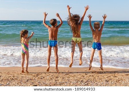 Four little kids jumping on the beach - stock photo