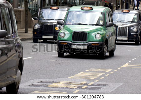 Four London Taxi Cabs in Canary Wharf (licence plate numbers removed) - stock photo