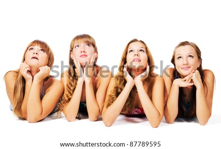 Four lovely girls laying on the floor together, isolated on white background - stock photo