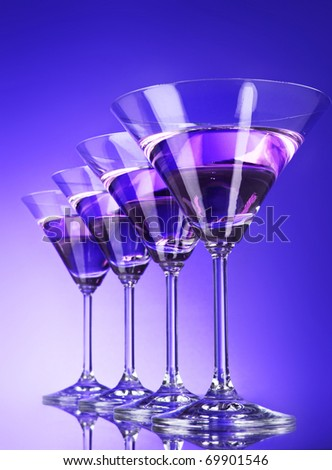 Four martini glasses on blue background - stock photo