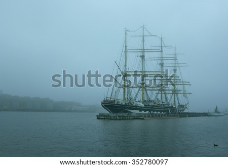 Four-masted sailing barque in the fog on the river processed with blue filter  - stock photo