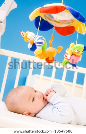 Four months old baby resting on crig at nursery and plying with his little thumb. Toys are officially property released. - stock photo