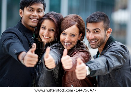 Four motivated trendy young Asian friends standing close together in a row giving a thumbs up of approval and success - stock photo