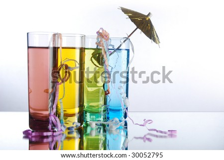 Four multi-colored shot glasses with colored alcohol on a reflective surface with party popper string and umbrella. - stock photo
