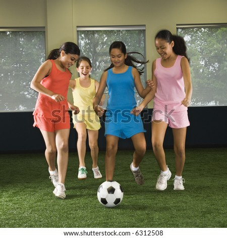 Four multiethnic girls playing soccer and laughing in indoor gym. - stock photo