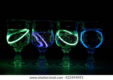Four neon glowing party drinks illuminated in the nightclub. - stock photo