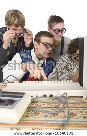 Four nerdy guys sitting in front of old-fashioned computer. One of them is pushing the button on keyboard. Side view, white background - stock photo