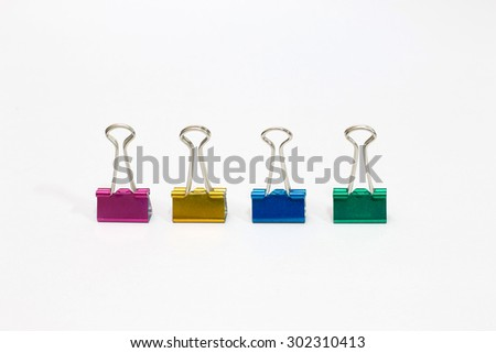 four office paper clips of different colors on a white background - stock photo