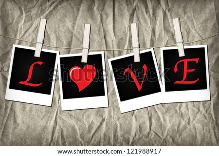 Four old-fashioned instant photos pegged to a clothesline, on grunge brown paper background with bleach-bypass effect.The word LOVE is spelled out across the images. - stock photo