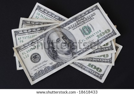 Four one hundred dollar bills isolated on black background - stock photo