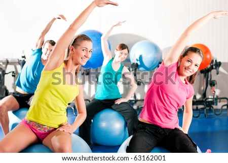 Four people - man and women - in the gym doing gymnastics on an exercise ball - stock photo