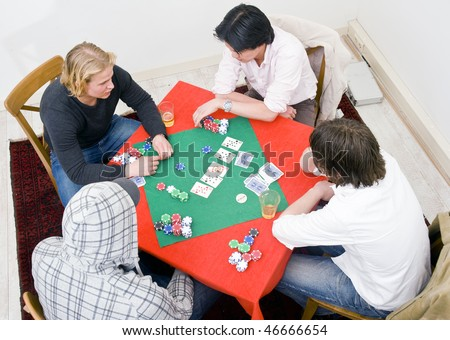 Four people sitting around a square poker table for a private casual game - stock photo