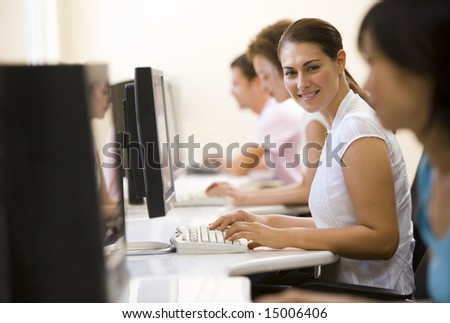 Four people sitting in computer room typing and smiling - stock photo