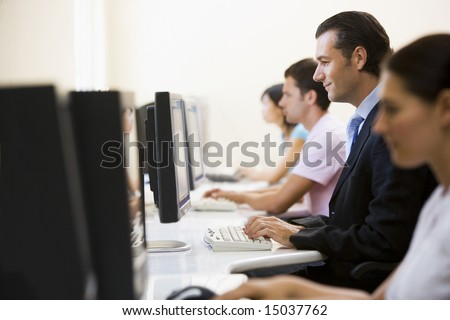 Four people sitting in computer room typing with one man in a suit - stock photo
