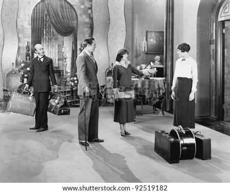 Four people standing in a the lobby of a hotel with luggage - stock photo
