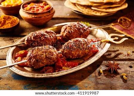 Four pieces of Indian style meat on skewers sitting in hot sauce with spices and bread around the plate - stock photo