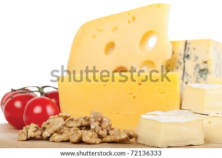 Four popular kinds of cheese ,tomatoes and walnut on a white background. A shot horizontal, focus in the shot foreground. - stock photo