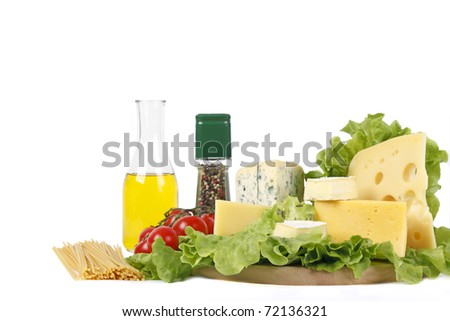 Four popular kinds of cheese, tomatoes, spices, macaroni and an olive oil bottle lie on salad sheet on a white background. A shot horizontal, focus in the shot foreground. - stock photo