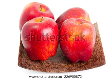 four red apples on a wooden plate - stock photo