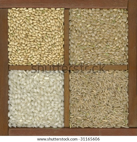 four rice grains in a primitive wooden box or drawer with dividers - left bottom white arborio (risotto) and, clockwise, three brown varieties: sweet (sushi), short, long grain - stock photo